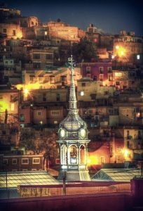 a steeple lit up at night with a hill populated with lots of houses behind it
