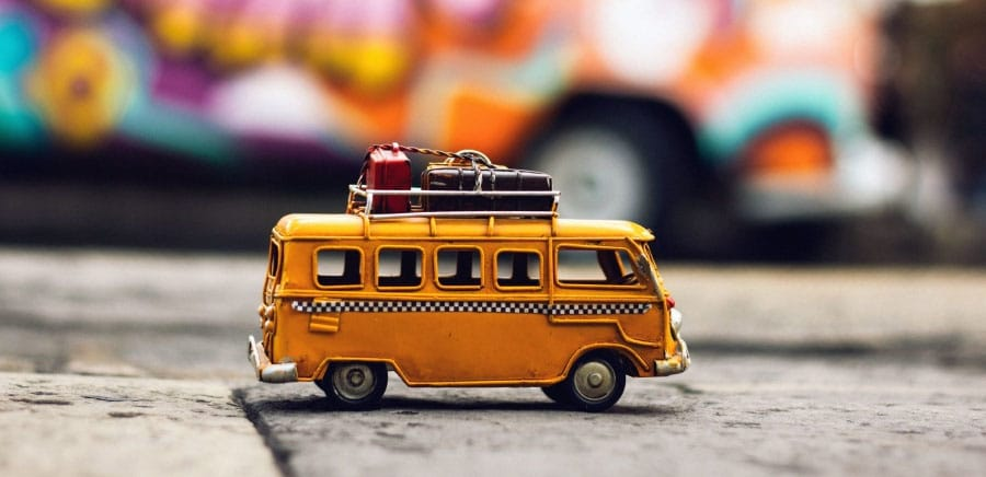 a toy bus with suitcases on it in front of a graffiti wall