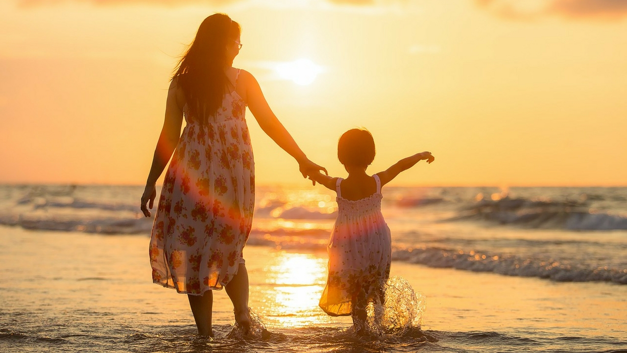 Young Mother On The Beach With Daughter At Sunset