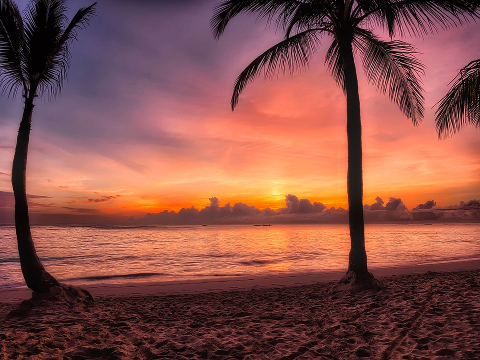 sunrise at dominican republic beach, the sun just above the horizon and the sky purple, pink and orange