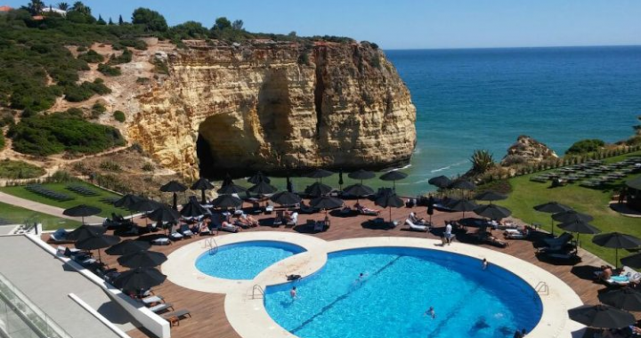 image of hotel swimming pool in portugal from high vantage point. rocks and the sea are in the background