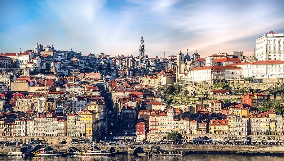 View from the river of porto in portugal leading upto spire at top of image