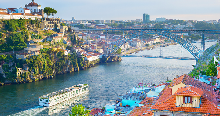 Panoramic view of the river valley in Porto, Portugal, as a river cruise ship prepares to pass under a bridge spanning the river valley