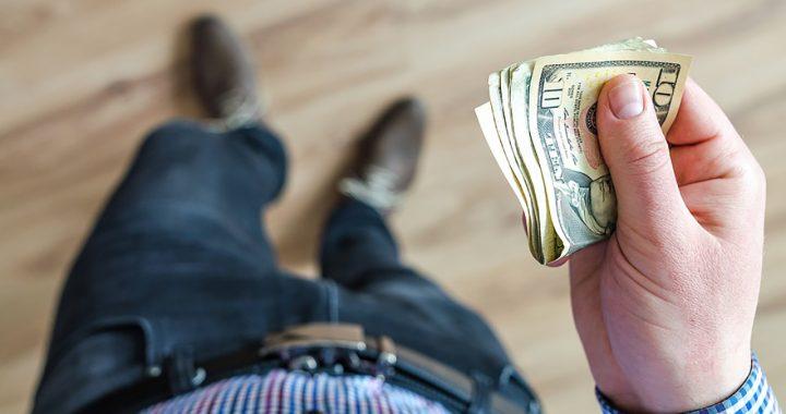 Man holding wad of U.S. dollars in cash