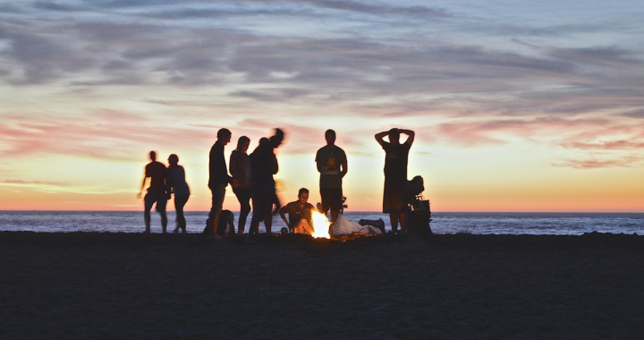 Friends enjoy a fire at the beach at sunst
