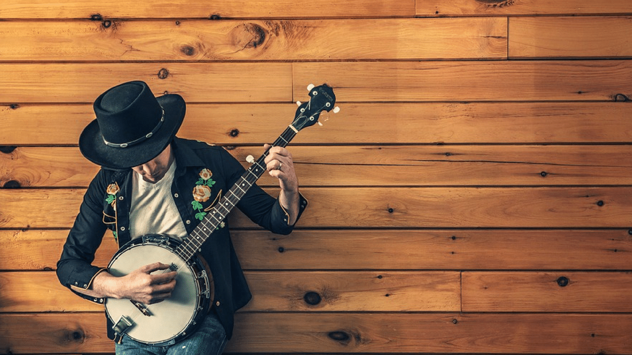 A man plays a banjo next to a wooden wall
