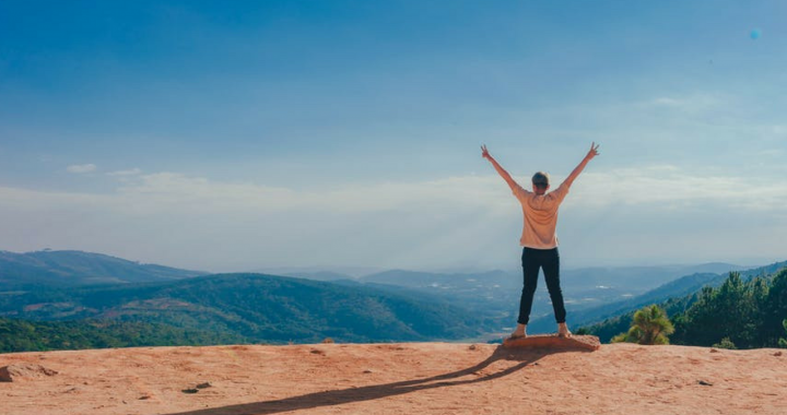 Person holding his arms in the air looking out over the mountains