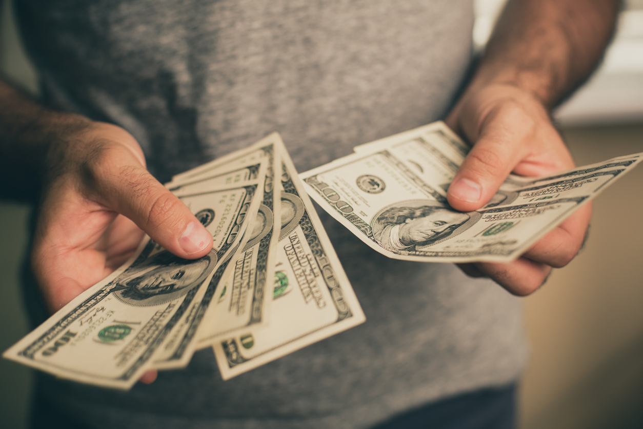 A man in a gray T-shirt holds dollars in his hands