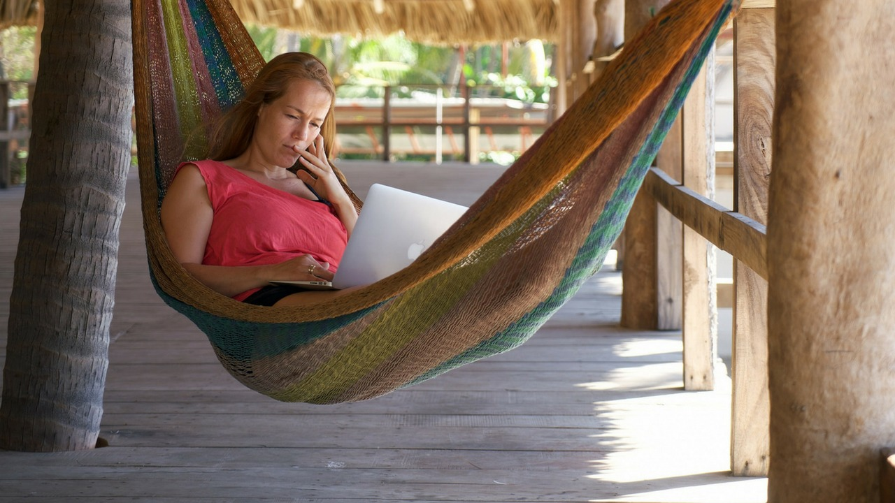 A woman works at her laptop in a hammock