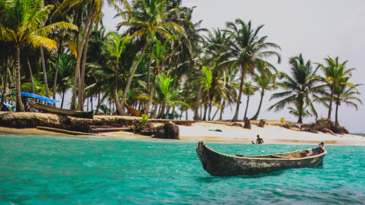 a traditional canoe in San Blas with blue water and palm trees