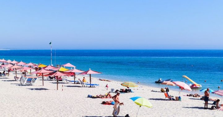 portugal bech with umbrellas and people enjoying the sun