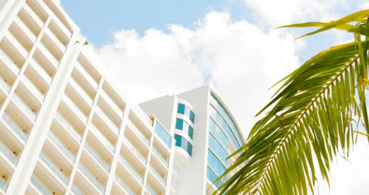 view of the westin playa bonita hotel in panama city, blue sky and a palm tree can be seen