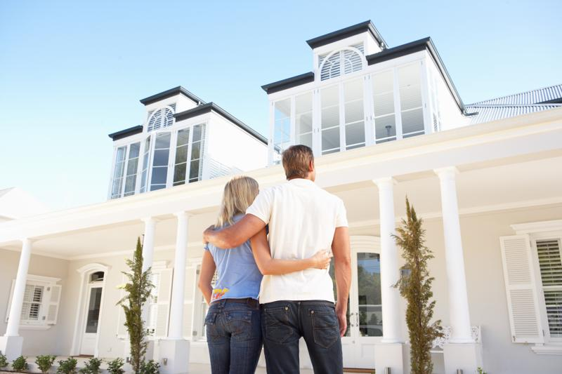 a couple looking up to their brand new home overseas, a white 2 story house with collums on the outside