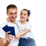 Dad with hands up holding two passports and daughter. Second residency concept.