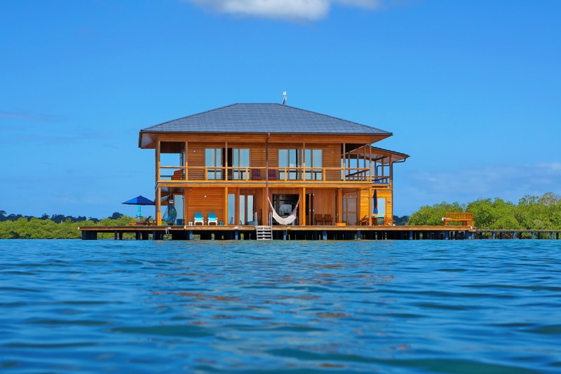 Wooden tropical home on stilts over water of the Caribbean sea, Panama.