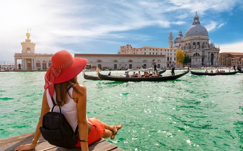 Women enjoys the view to the Basilica di Santa Maria della Salute and Canale Grande in Venice, Italy