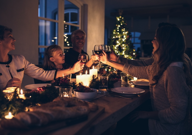 Family toasting with wine in a Christmas dinner at home in the living room.