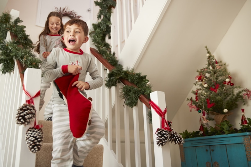 Two Excited Children Wearing Pajamas Running Down Stairs Holding Stockings On Christmas Morning.