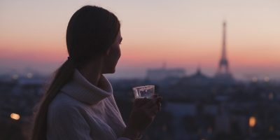 Woman enjoying beautiful panoramic view of Paris with cup of coffee.