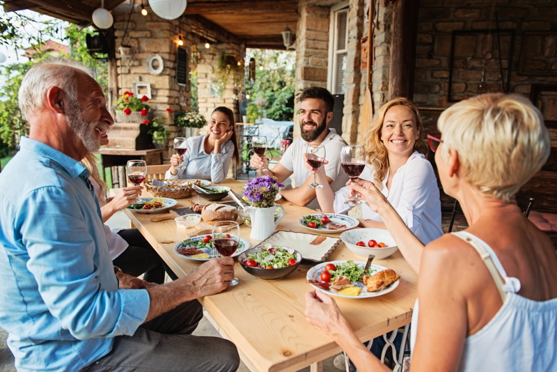 Family cheering over the dining table outdoors.