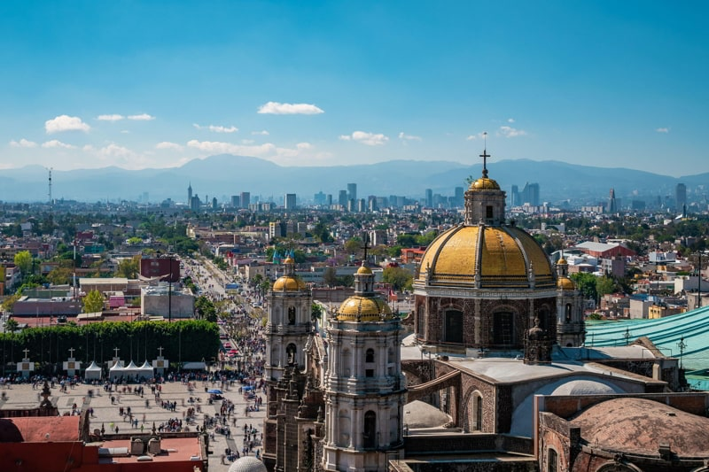 Mexico City, Mexico, Basilica of Our Lady of Guadalupe with Mexico City skyline in the background.